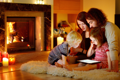 Depositphotos 52801729 s 2015 - Happy family using a tablet pc by a fireplace